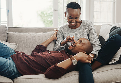 Buy stock photo Shot of a happy young couple spending time and relaxing together on a couch at home