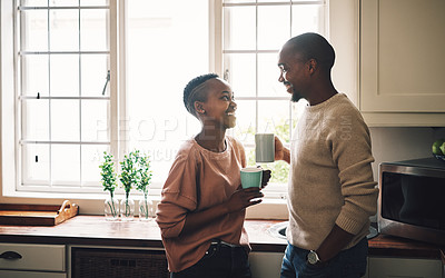Buy stock photo Shot of a happy young couple drinking coffee and spending time together at home