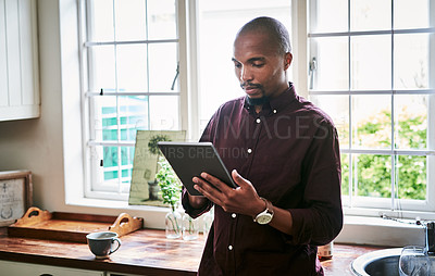 Buy stock photo Shot of a handsome young businessman using a digital tablet while working from home during the day