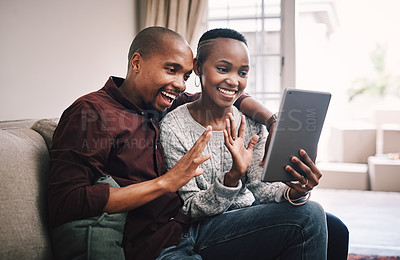 Buy stock photo Shot of a happy young couple using their digital tablet to make a video call while relaxing together at home