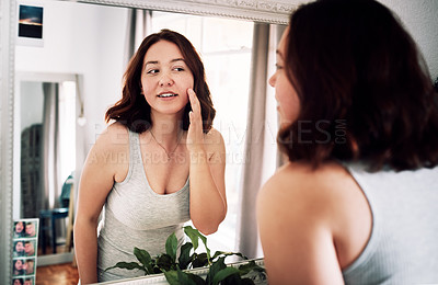 Buy stock photo Cropped shot of an attractive young woman inspecting her face while standing in front of the mirror in her bedroom at home