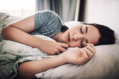 Buy stock photo Cropped shot of an attractive young woman sleeping on her bed in the morning at home