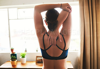 Buy stock photo Rearview shot of an attractive young woman standing in her room and stretching her tricep after a workout at home