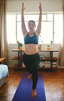 Buy stock photo Cropped shot of an attractive young woman standing and holding a warrior pose while doing yoga in her home