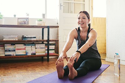 Buy stock photo Cropped shot of an attractive young woman sitting and holding a seated forward bend while doing yoga in her home