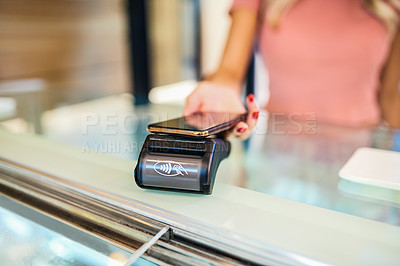 Buy stock photo Shot of a woman paying at the checkout of an ice cream parlour with her smartphone