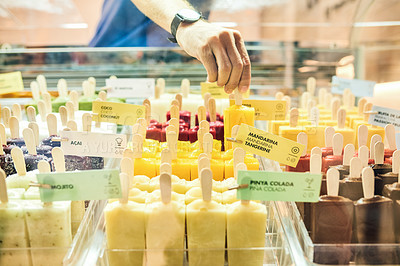 Buy stock photo Cropped shot of a man arranging the ice cream display in his store