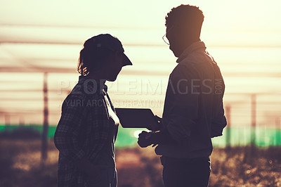 Buy stock photo Cropped shot of two unrecognizable farmers looking at a tablet while working on their farm
