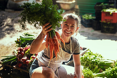 Buy stock photo Portrait of an attractive young female farmer holding a bunch of freshly picked carrots at her farm