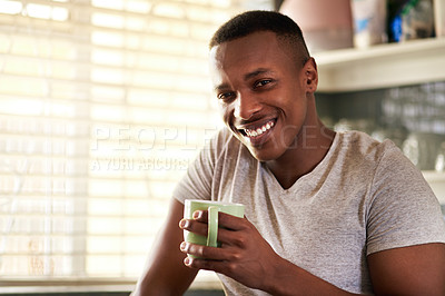 Buy stock photo Cropped portrait of a handsome young man smiling while having a cup of coffee in his kitchen at home