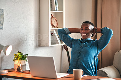 Buy stock photo Cropped shot of a handsome young businessman sitting in his home office with his hands behind his head in accomplishment