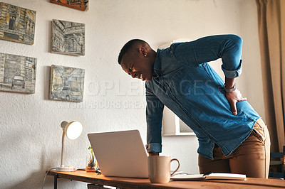 Buy stock photo Cropped shot of a handsome young businessman standing alone in his office and suffering from back pain