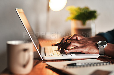 Buy stock photo Cropped shot of an unrecognizable businessman sitting alone in his home office and working on his laptop