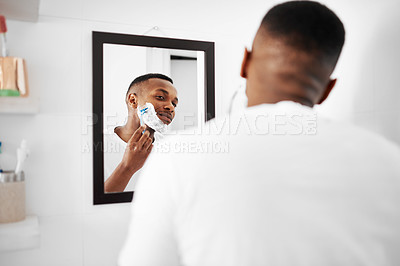 Buy stock photo Cropped shot of a young man applying shaving foam to his face