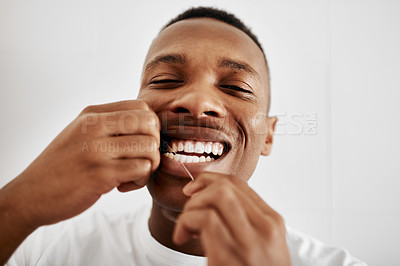 Buy stock photo Cropped shot of a young man flossing his teeth in the bathroom at home