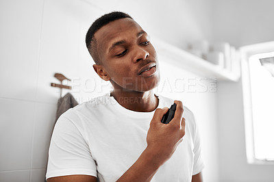 Buy stock photo Shot of a young man spraying himself with deodorant