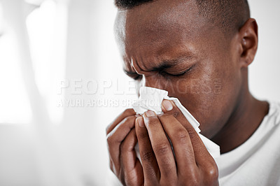 Buy stock photo Cropped shot of a young man blowing his nose at home