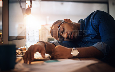 Buy stock photo Shot of a young businessman sleeping at his desk in an office at night