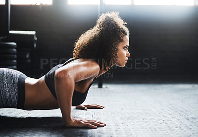 Buy stock photo Shot of a young woman doing pushups in a gym