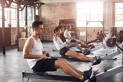 Buy stock photo Shot of a young woman working out with a rowing machine in the gym