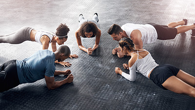 Buy stock photo Shot of a group of young people doing planks together during their workout in a gym