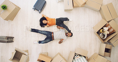 Buy stock photo High angle shot of a young couple lying on the floor and showing thumbs up while moving house