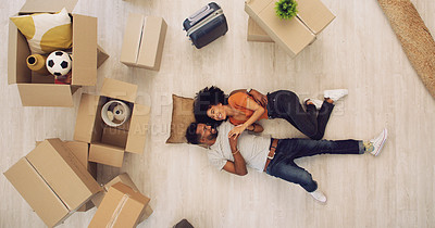 Buy stock photo High angle shot of a young couple lying on the floor while moving house