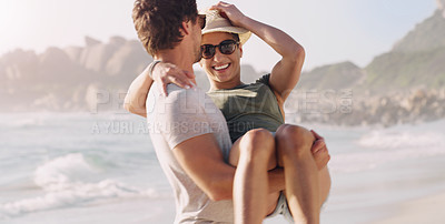 Buy stock photo Cropped shot of an affectionate young man carrying his girlfriend at the beach during the day