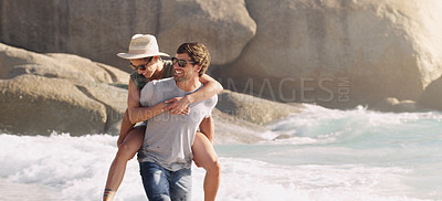 Buy stock photo Cropped shot of an affectionate young man piggybacking his girlfriend at the beach during the day
