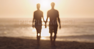 Buy stock photo Rearview shot of an unrecognizable couple holding hands while walking together at the beach at sunset