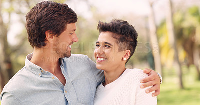 Buy stock photo Cropped shot of an affectionate young couple smiling at each other while standing in a park during the day