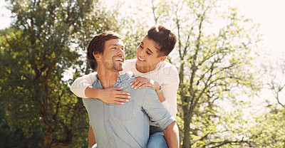 Buy stock photo Cropped shot of an affectionate young man piggybacking his girlfriend in a park during the day