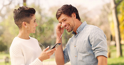 Buy stock photo Cropped shot of an affectionate young couple listening to music together on a pair of earphones in a park