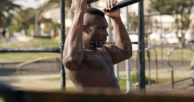 Buy stock photo Shot of a muscular young man working out at a calisthenics park