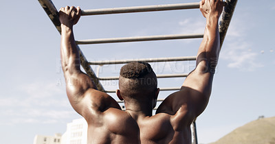 Buy stock photo Rearview shot of a muscular young man working out at a calisthenics park