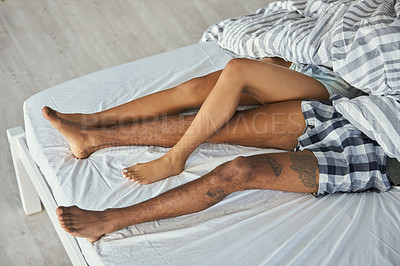 Buy stock photo Cropped shot of an unrecognizable couple lying in bed together