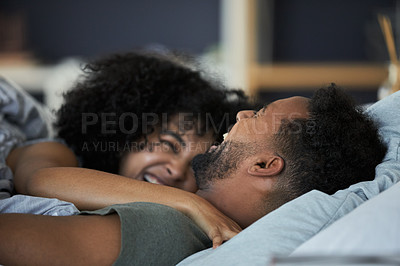 Buy stock photo Cropped shot of a happy young couple lying in bed together