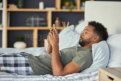Buy stock photo Cropped shot of a young man using his cellphone while lying in bed