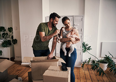 Buy stock photo Cropped shot of an affectionate young father showing his young baby girl a stuffed toy while opening boxes in their new home on moving day
