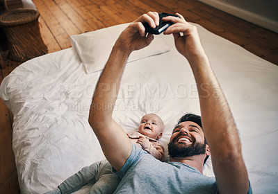 Buy stock photo High angle shot of an affectionate young father taking selfies with his little baby girl while lying on a bed at home