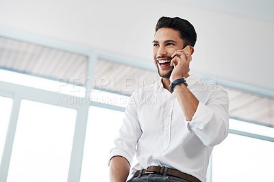 Buy stock photo Cropped shot of a handsome young businessman sitting in his office and talking on his cellphone