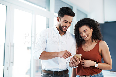 Buy stock photo Cropped shot of two young business colleagues standing together in the office and using a cellphone