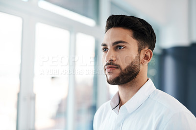 Buy stock photo Cropped shot of a handsome young businessman looking contemplative while standing in his office alone