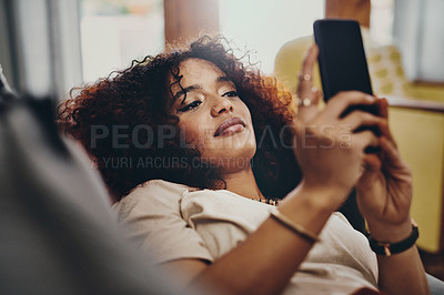 Buy stock photo Shot of an attractive young woman using her cellphone while relaxing on the sofa at home