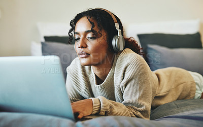 Buy stock photo Shot of a young woman wearing headphones while using her laptop at home