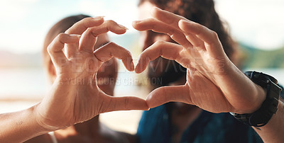 Buy stock photo Cropped shot of an unrecognizable couple making a heart shape with their hands while standing on the beach