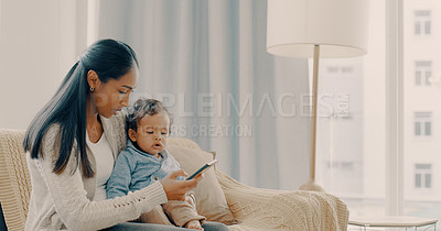 Buy stock photo Shot of a young mother using her cellphone while spending time with her baby boy at home