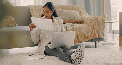 Buy stock photo Full length shot of an attractive young woman using a laptop while sorting out her paperwork at home