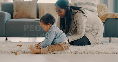 Buy stock photo Full length shot of a happy young mother bonding and playing with her adorable baby boy at home