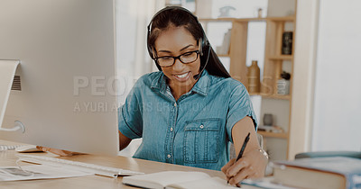 Buy stock photo Shot of an attractive young businesswoman wearing headsets and working on a computer at home